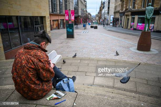 Man reads a book on the steps of The Royal Concert Hall on March 27, 2020 in Glasgow, Scotland.Scotland. First Minister of Scotland Nicola Sturgeon...