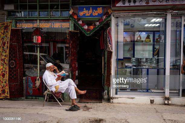 A man reads a book outside a carpet store in Kabul Afghanistan on Thursday July 12 2018 US President Donald last year said 16000 US troops would...