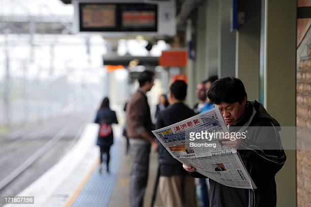 A man reads a copy of the Australian Chinese Daily newspaper while waiting for a train at Cabramatta station in western Sydney Australia on Tuesday...