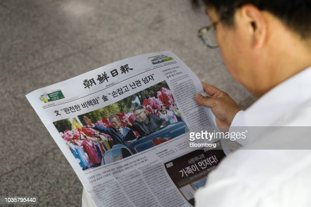 A man reads a copy of the Chosun Ilbo newspaper featuring a photograph of North Korean Leader Kim Jong Un and South Korean President Moon Jaein on...