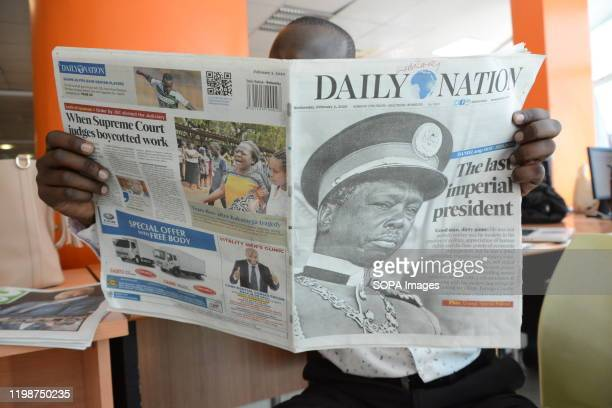 A man reads a copy of The Daily Nation newspaper that reports the death of Daniel Arap Moi Former President of Kenya Daniel Arap Moi died aged 95...