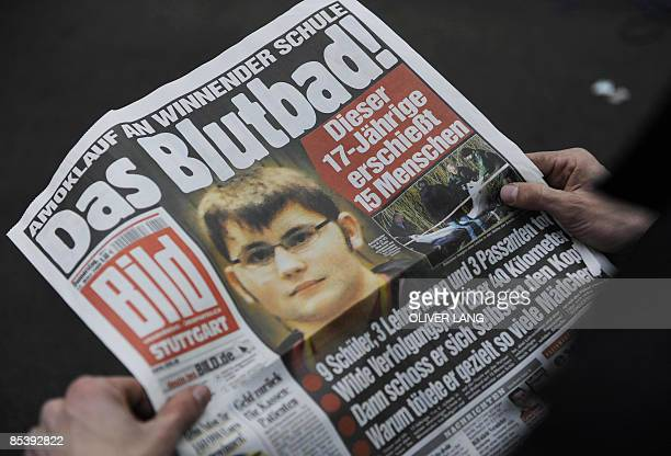 A man reads a copy of the German tabloid newspaper 'Bild' in Winnenden southern Germany on March 12 2009 A teenager in black combat gear went on the...