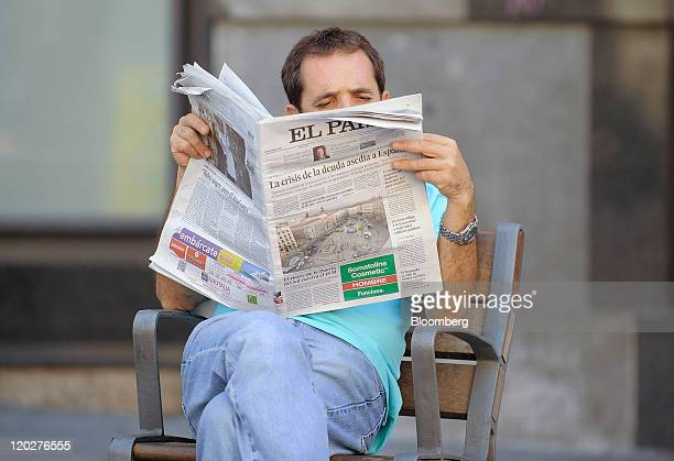A man reads a copy of the Spanish newspaper El Pais with the front page story of the Spanish and Italian bond crisis in Madrid Spain on Wednesday Aug...