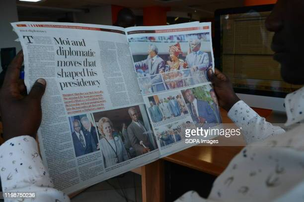 A man reads a copy of The Standard newspaper that reports the death of Daniel Arap Moi Former President of Kenya Daniel Arap Moi died aged 95 while...