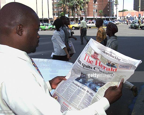 A man reads a copy of the stateowned Herald newspaper in Harare 08 December 2003 a day after Zimbabwean President Robert Mugabe told the leaders of...