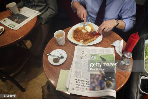 Man reads a copy of 'The Times' newspaper while eating his breakfast in a cafe on November 28, 2012 in London, England. The findings of the Leveson...