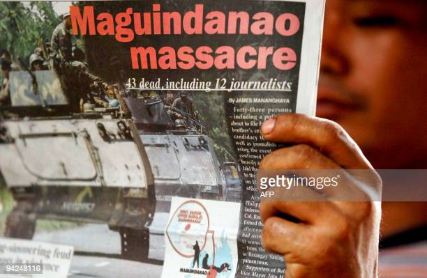 A man reads a daily newspaper that runs a front page story about the massacre that claimed the lives of at least 35 people including 12 journalists...
