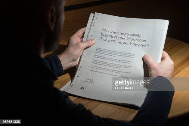A man reads a fullpage advertisment taken out by Mark Zuckerberg the chairman and chief executive officer of Facebook to apologise for the largescale...