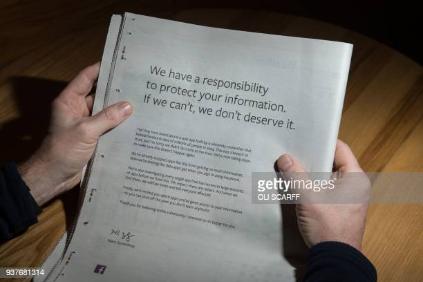 TOPSHOT A man reads a fullpage advertisment taken out by Mark Zuckerberg the chairman and chief executive officer of Facebook to apologise for the...