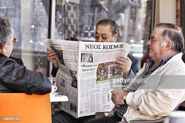 A man reads a Greeklanguage newspaper at a cafe in Oakleigh a suburb of Melbourne Australia on Tuesday June 12 2012 Armed with patriotism and the...