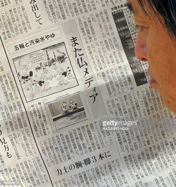 A man reads a Japanese local newspaper reporting cartoons published in a French newspaper in Tokyo on September 12 2013 Japan voiced anger September...