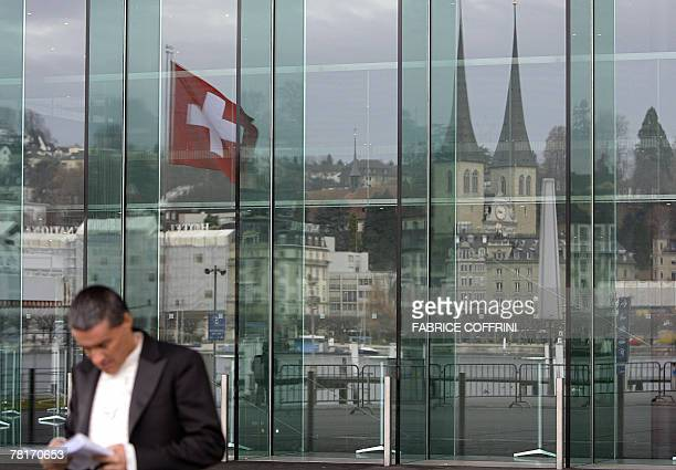 A man reads a map in front of the Lucerne's landmarks reflected on the windows of the Culture and Convention Center 30 November 2007 that will host...