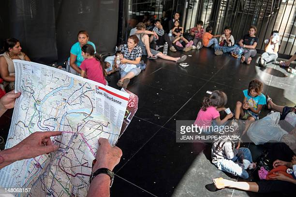 A man reads a map of Lyon city as Roma from Macedonia Kosovo and Bulgaria evicted from the train station where they settled their camp found shelter...