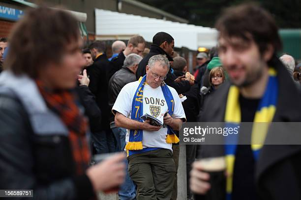 A man reads a match programme outside AFC Wimbledon's stadium before the npower League Two match between AFC Wimbledon and Aldershot Town at the...