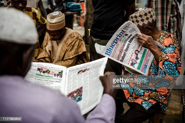 TOPSHOT A man reads a national newspaper with a headline announcing the victory of the incumbent President Muhammadu Buhari following Nigeria's...