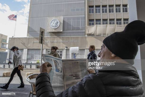 TOPSHOT A man reads a newspaper as he sits in a café outside the US embassy in Tel Aviv on December 6 2017 President Donald Trump is set to recognise...