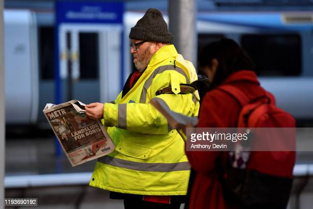 Man reads a newspaper at a tram stop in Manchester city centre after the Conservative Party won a majority in the 2019 UK General Election on...
