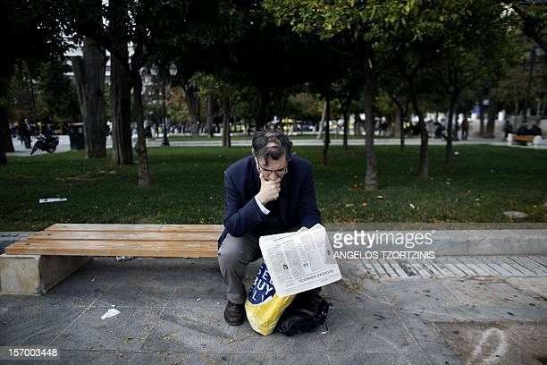 A man reads a newspaper at Syntagma square in Athens on November 27 2012 The eurozone and IMF saved Greece with a redrawn rescue to avert bankruptcy...