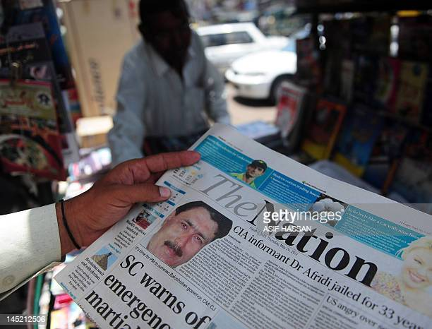 A man reads a newspaper bearing the photograph of Pakistani surgeon Shakeel Afridi recruited by the CIA to help find Osama bin Laden at a newsstand...