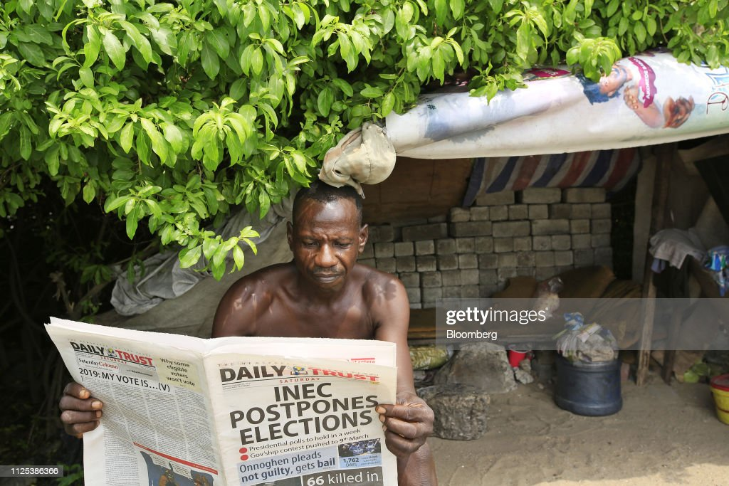 A man reads a newspaper displaying a headline 'Inec postpones