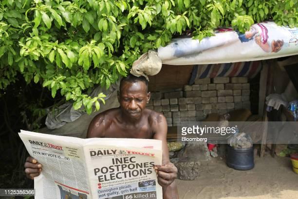 A man reads a newspaper displaying a headline Inec postpones elections in Lagos Nigeria on Saturday Feb 16 2019 A lastminute delay of Nigerias...
