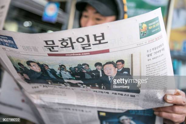 A man reads a newspaper featuring a photograph of Cho Myounggyon South Korea's unification minister left shaking hands with Ri Son Gwon chairman of...