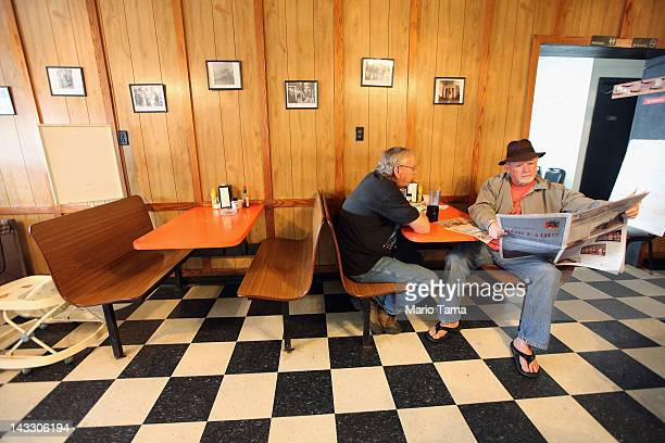 A man reads a newspaper in a restaurant on April 22 2012 in Booneville Kentucky Daniel Boone once camped in the Appalachian mountain hamlet of Owsley...