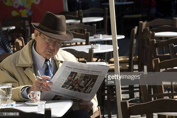 Man reads a newspaper in Athens on November 5, 2011. In the packed shops of Athens, people were worried more about their financial future than...
