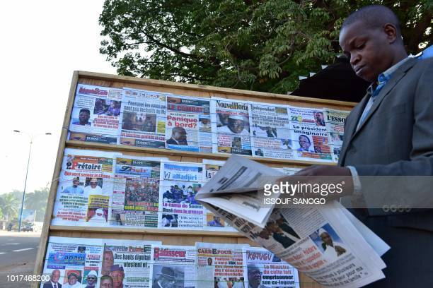 A man reads a newspaper in Bamako on August 16 ahead of the announcement of the results of Mali's presidential election Results for the runoff vote...