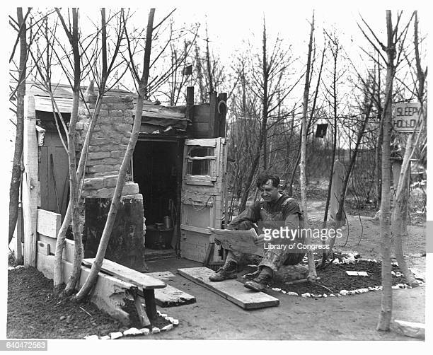 A man reads a newspaper in front of his shack at Chicago shantytown during the Great Depression The shantytown's site became the grounds for the 1933...