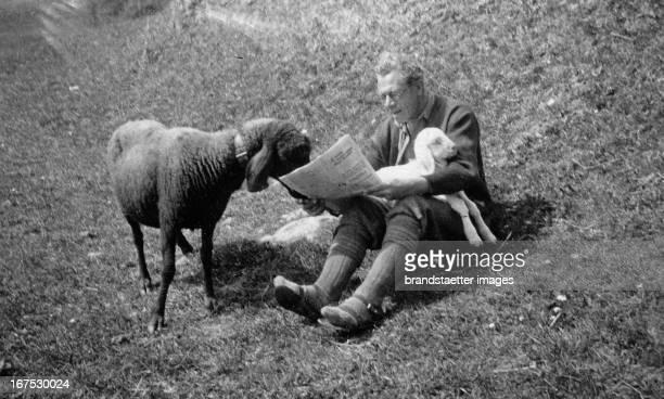 Man reads a newspaper in the presence of two sheep. About 1940. Photograph. Ein Mann liest Zeitung in Anwesenheit von zwei Schafen. 1939....