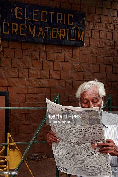 A man reads a newspaper just outside the Chandanwadi Crematorium on November 30 2008 in Mumbai India The city of Mumbai was rocked by multiple...