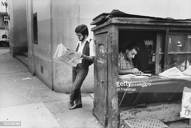A man reads a newspaper leaning against a news stand in New York City 1979