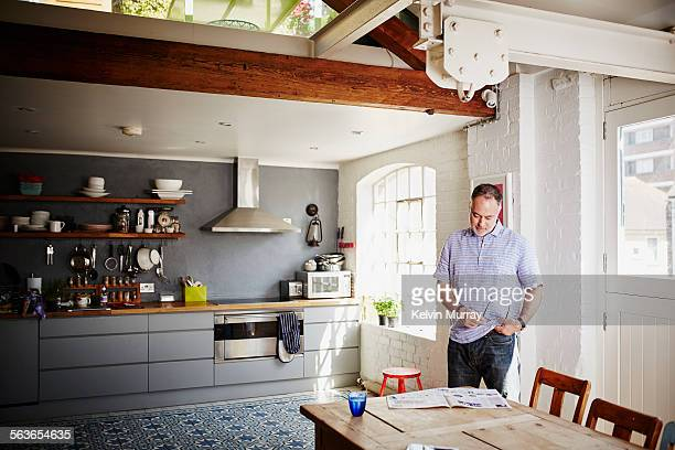 A man reads a newspaper on his dining table