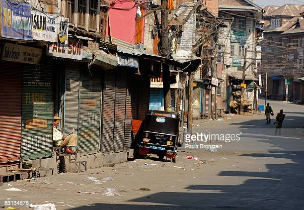 A man reads a newspaper on the empty streets as Indian security forces stand guard during a curfew October 5 2008 in Srinagar Kashmir India A strict...