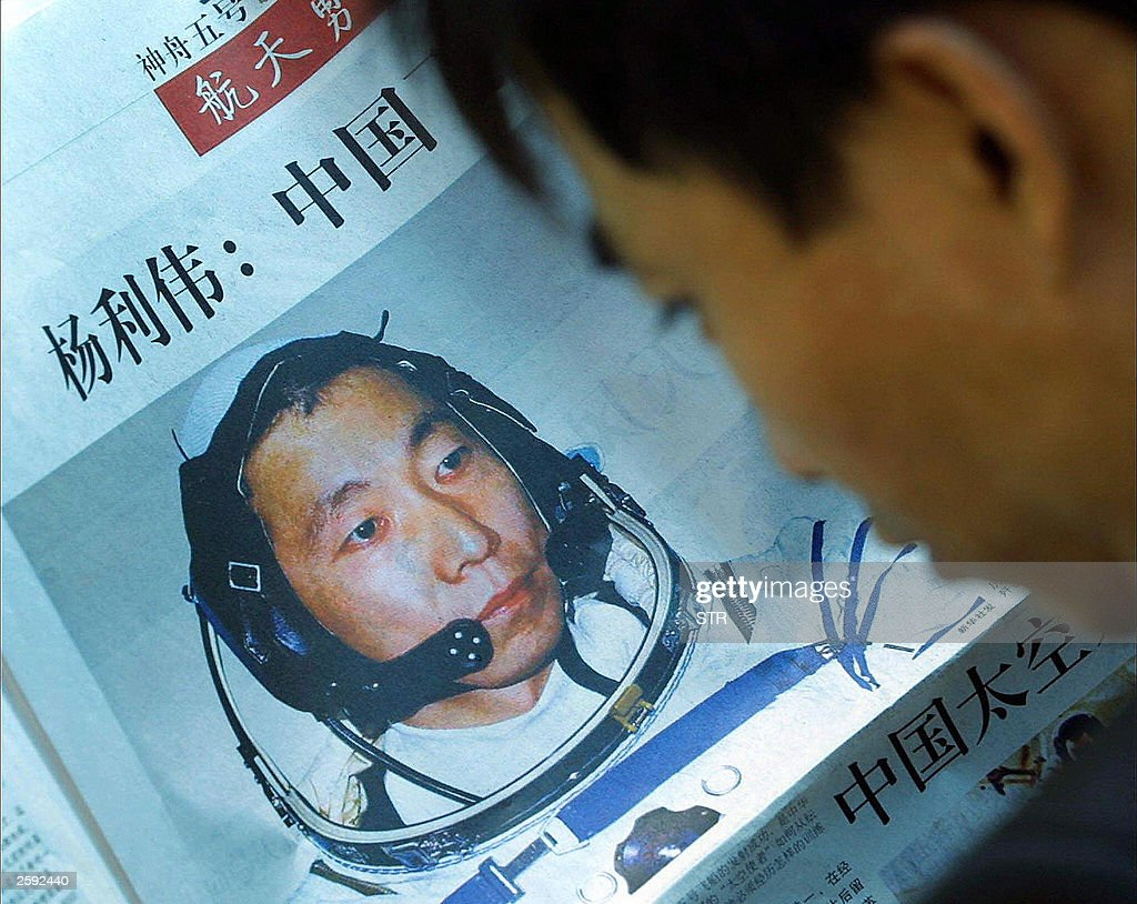A man reads a newspaper profiling Chines : News Photo