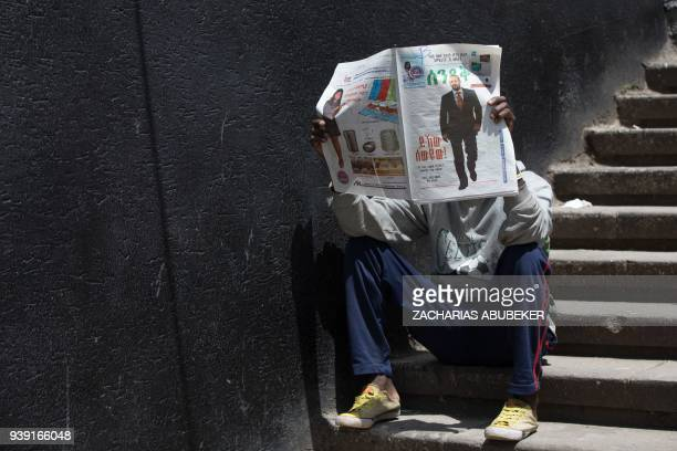 A man reads a newspaper showing the news of newly elected leader of Ethiopia's ruling coalition Ethiopian Peoples' Revelutionary Democratic Front in...