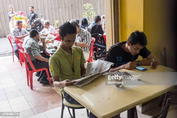 Man reads a newspaper while having a morning tea in a restaurant in Kuala Lumpur, Malaysia, on Tuesday, March 18, 2014. Malaysia, aspiring to become...