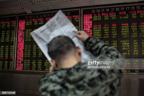 A man reads a newspaper while keeping an eye on stock price movements displayed on a screen at a securities company in Beijing on March 23 2018 Hong...