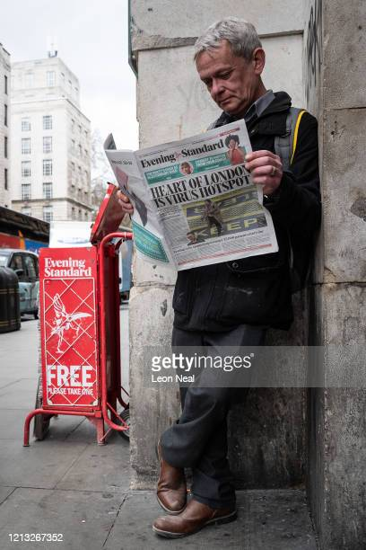 """Man reads a newspaper, with a headline warning """"Heart Of London Is Virus Hotspot"""" on March 18, 2020 in London, England. Wales and Scotland have today..."""