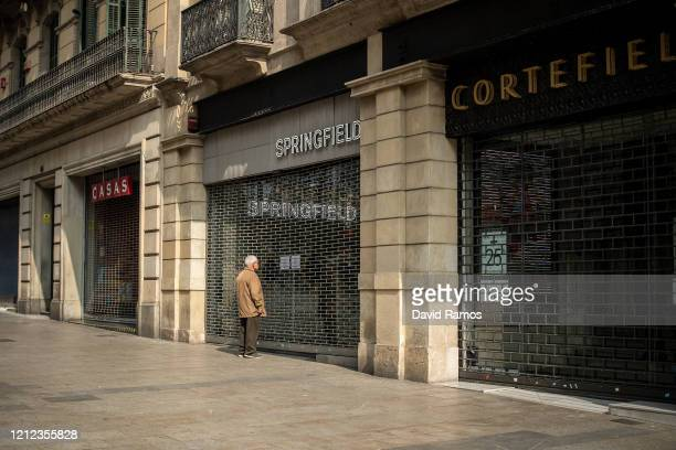 A man reads a note in a Springfield fashion store closed as measure against the coronavirus expansion on March 14 2020 in Barcelona Spain The Catalan...