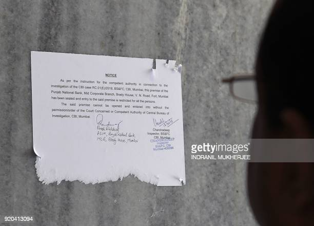 A man reads a notice by the Indian Central Bureau of Investigation stating that the Brady House branch of the Punjab National Bank has been sealed...