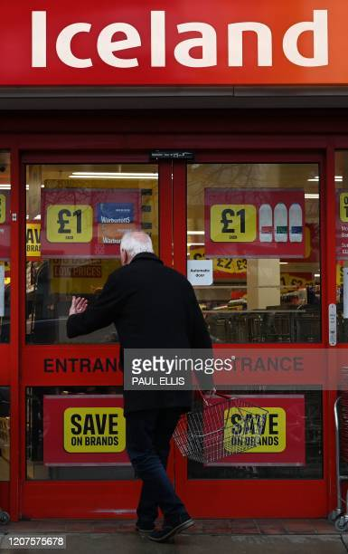 A man reads a notice stating new opening times for an Iceland supermarket in Liverpool north west England on March 18 2020 Many supermarkets are...