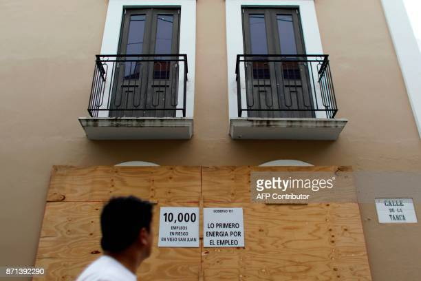 A man reads a noticeon a closed down business asking for local business owners to protest against the Puerto Rico Power Authority because of the lack...