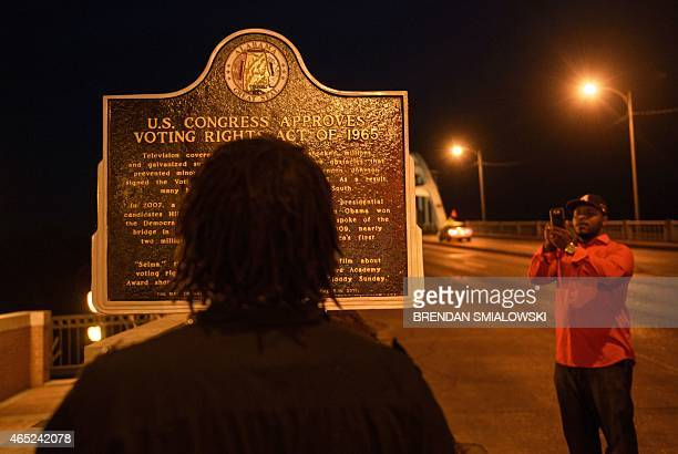 Man reads a plaque describing the 1965 Voting Rights Act at the base of the Edmund Pettus Bridge, where route 80 crosses the Alabama River, on March...