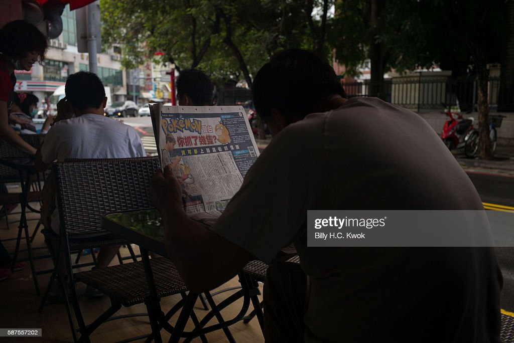 A man reads a Pokemon Go article in the newspaper on August 7, 2016 in Tainan, Taiwan. 'Pokemon Go,' which has been a smash-hit across the globe was launched in Taiwan on 6th August. Since its global launch, the mobile game has been an unexpected megahit among users who have taken to the streets with their smartphones.