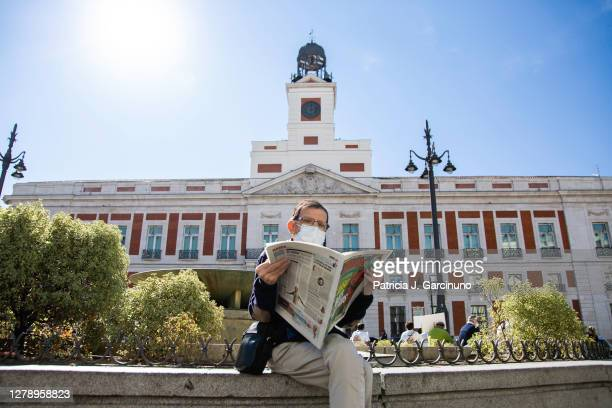 Man reads a sports newspaper sitting at Puerta del Sol, with the headquarters of the Community of Madrid behind him on October 06, 2020 in Madrid,...