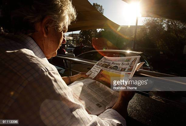A man reads about the dust storm in a local newspaper whilst his car is being washed on September 24 2009 in Sydney Australia Sydney was yesterday...