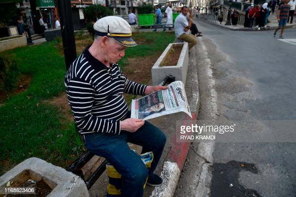 A man reads an Algerian Arabiclanguage newspaper with its cover dominated by the announced Algerian presidential election date as he sits along a...