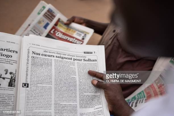 Man reads an article in the L'Observateur Paalga newspaper in Ouagadougou on June 7 about the attacks that happened in Solhan. - Suspected jihadists...